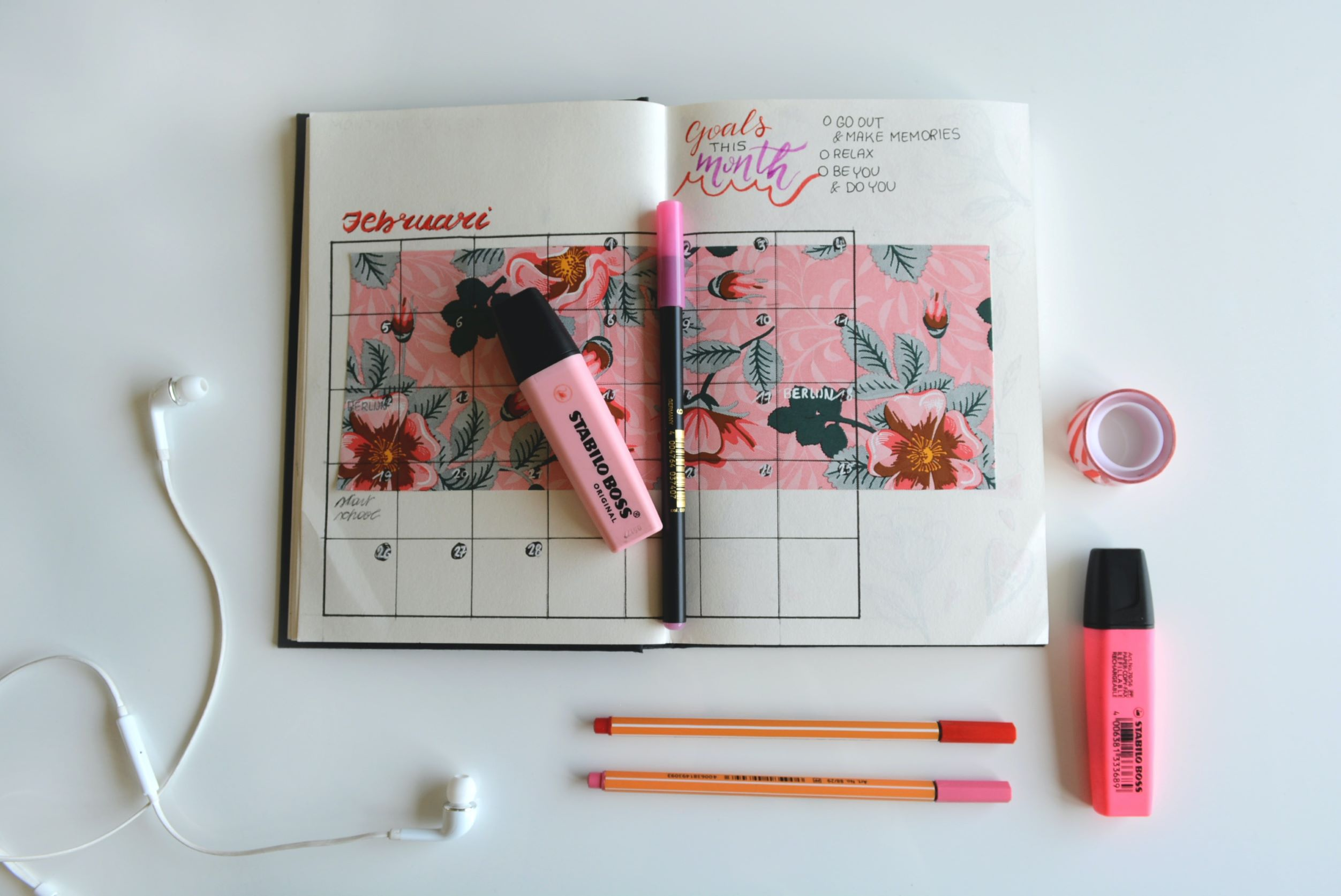 Pink planner, pens, highlighters and washi tape