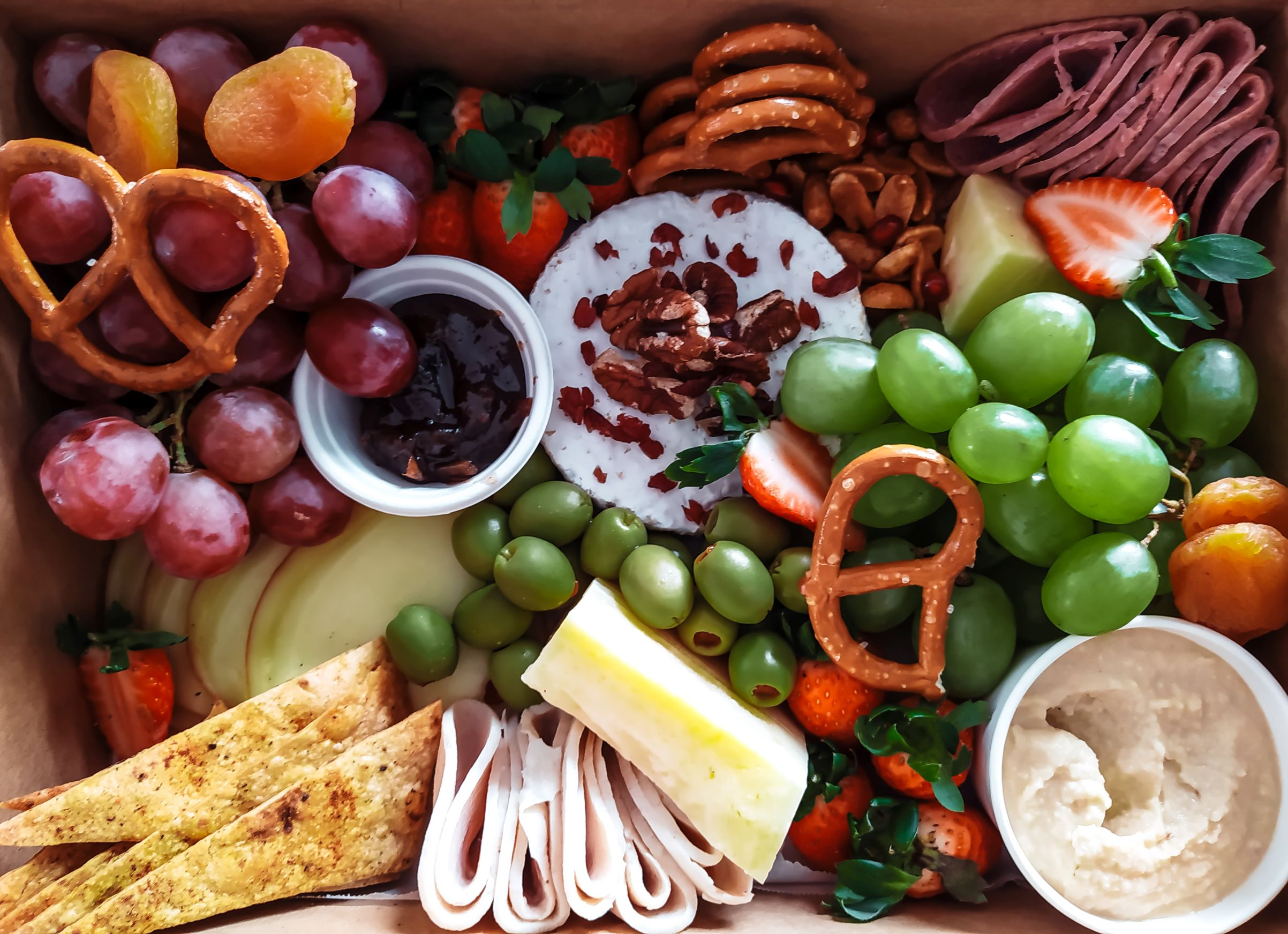 food platter with pretzels, fruit, deli meat, and cheese