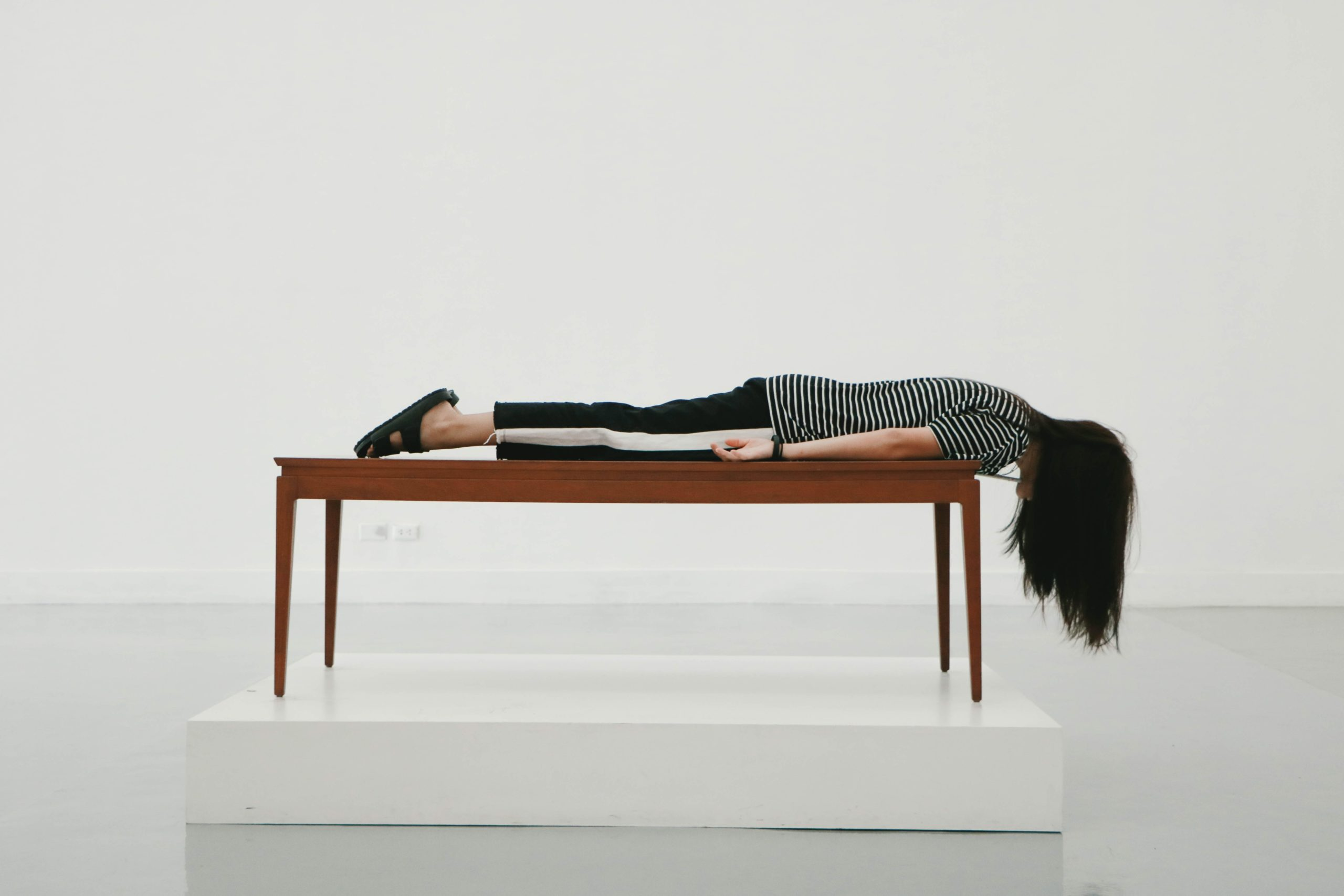 A woman lies facedown on a table to represent an exhausted student during finals week.