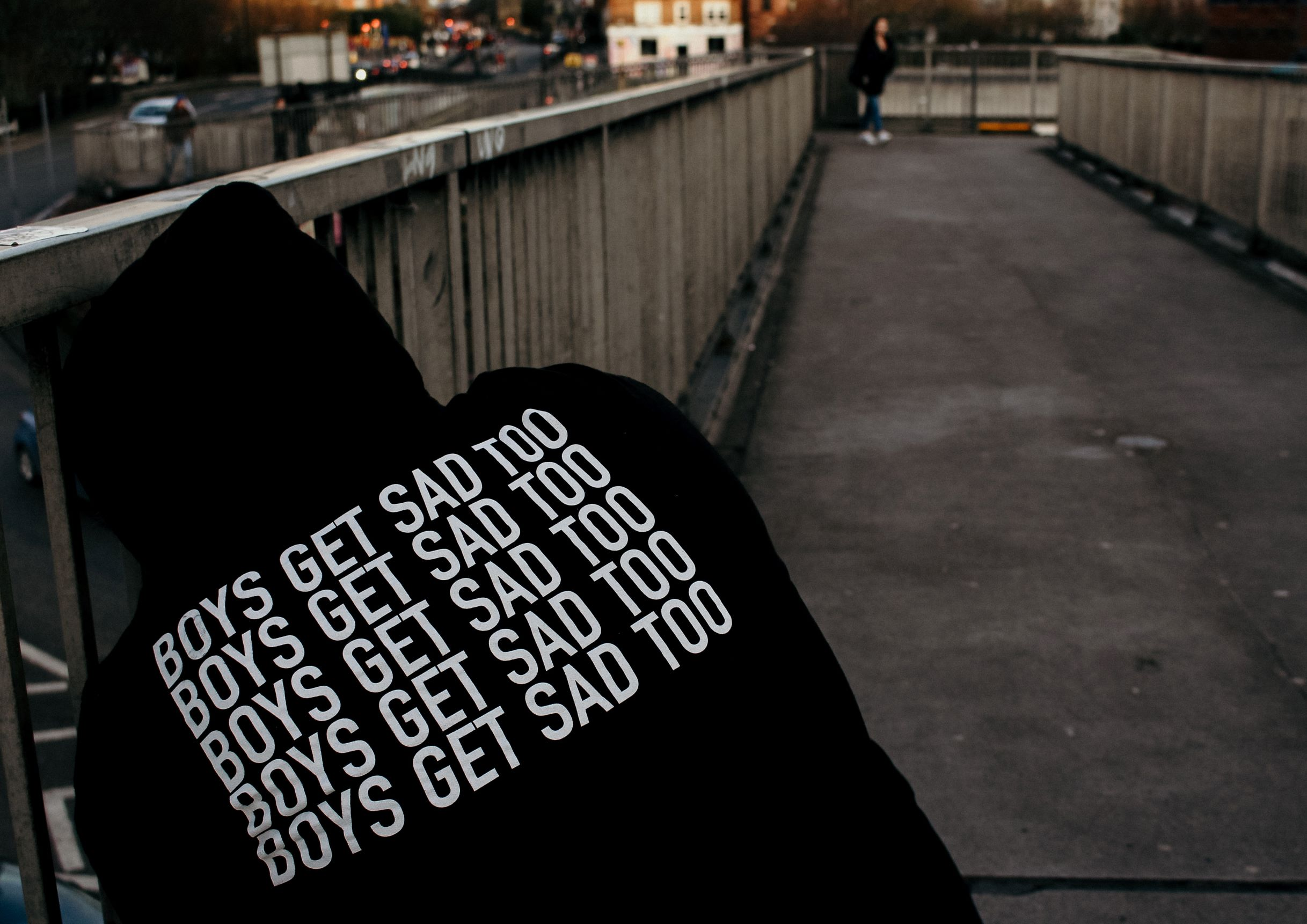 """Back of a person wearing a black sweatshirt that says """"Boys Get Sad Too."""" Colors are dark to represent depression in men."""